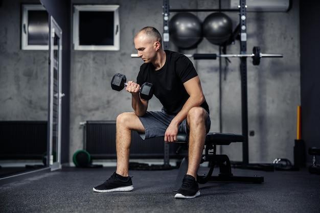 Mężczyzna w czarnej koszulce, siedząc na siłowni, unosi hantle jedną ręką