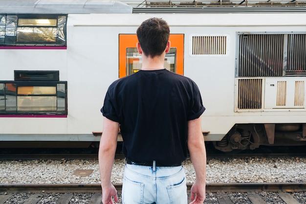 Mężczyzna w czarnej koszulce stojący przed pociągiem kolejowym