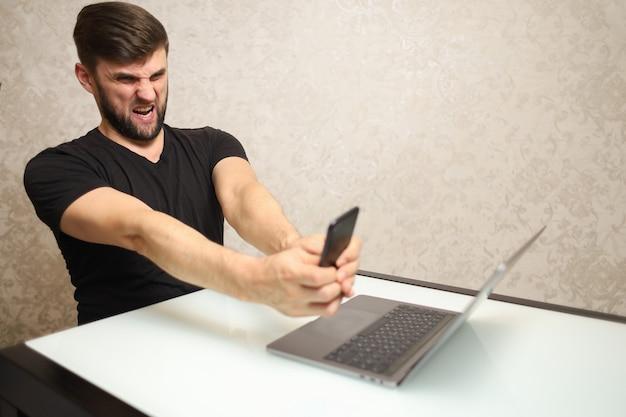 Mężczyzna w czarnej koszulce wskazuje na swojego laptopa