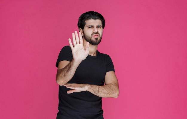 Mężczyzna w czarnej koszuli czegoś nie chce i odrzuca to