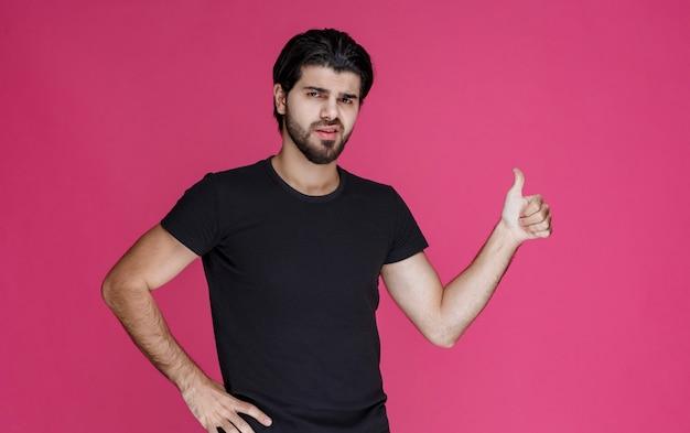 Mężczyzna w czarnej koszuli czuje się z czymś pozytywnie i cieszy się z tego