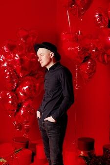 Mężczyzna w czarnej koszuli i kapeluszu stoi z balonami w kształcie serca