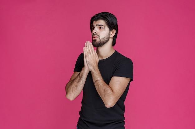 Mężczyzna w czarnej koszuli modli się i marzy o czymś