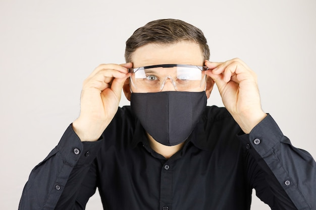 Mężczyzna w czarnej koszuli nosił okulary medyczne na białym tle