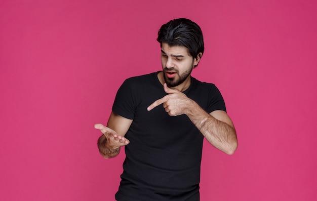 Mężczyzna w czarnej koszuli pokazuje coś w ręku