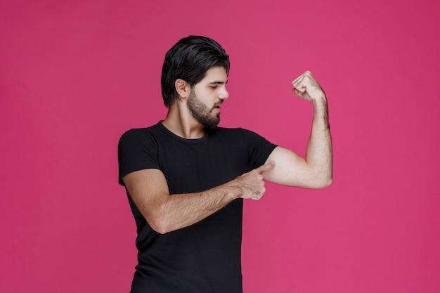 Mężczyzna w czarnej koszuli pokazuje mięśnie ramion