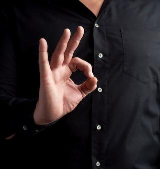 Mężczyzna w czarnej koszuli pokazuje prawy symbol ok