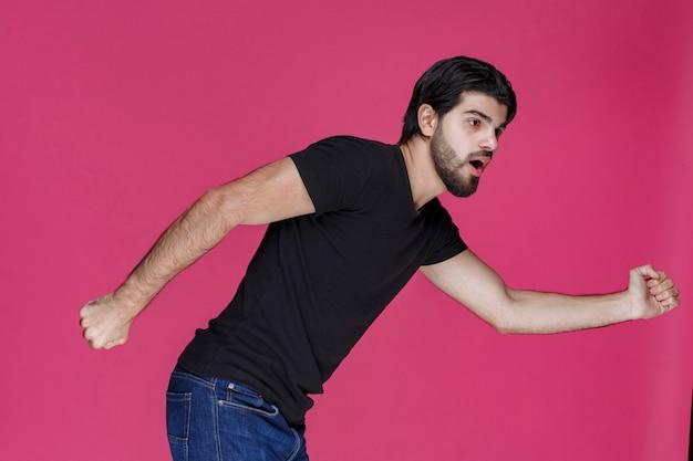 Mężczyzna w czarnej koszuli spieszy się i ucieka z sytuacji