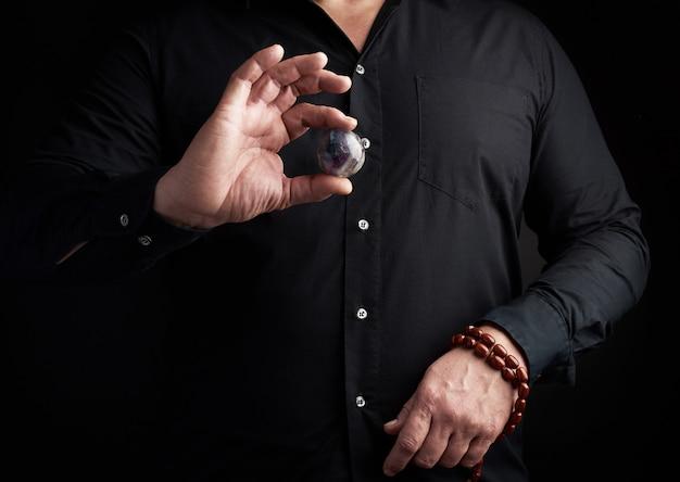 Mężczyzna w czarnej koszuli trzyma kamienną piłkę do rytuałów religijnych
