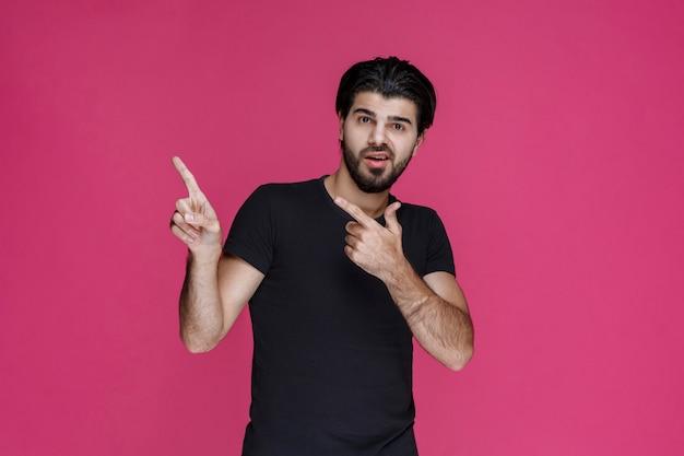Mężczyzna w czarnej koszuli, wskazujący na coś lub przedstawiający kogoś