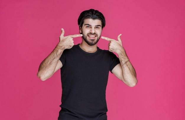 Mężczyzna w czarnej koszuli wskazuje usta i pyta z uśmiechem