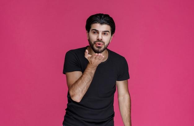 Mężczyzna w czarnej koszuli wygląda na zrelaksowanego, fajnego i zalotnego