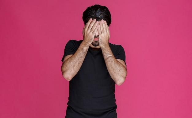 Mężczyzna w czarnej koszuli zasłania twarz, żeby się ukryć