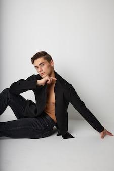 Mężczyzna w czarnej kurtce siedzi na podłodze na białym tle casual wear studio luksus.