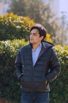 Mężczyzna w czarnej kurtce stoi w parku i czeka na kogoś. zdjęcie wysokiej jakości