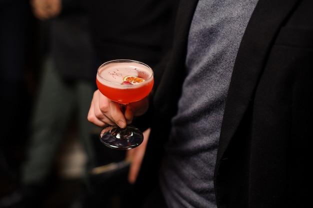 Mężczyzna w czarnej kurtce trzyma kieliszek koktajlowy ze słodkim napojem alkoholowym
