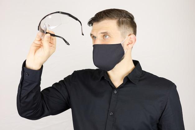 Mężczyzna w czarnej masce ochronnej patrzy w okulary medyczne na białym tle