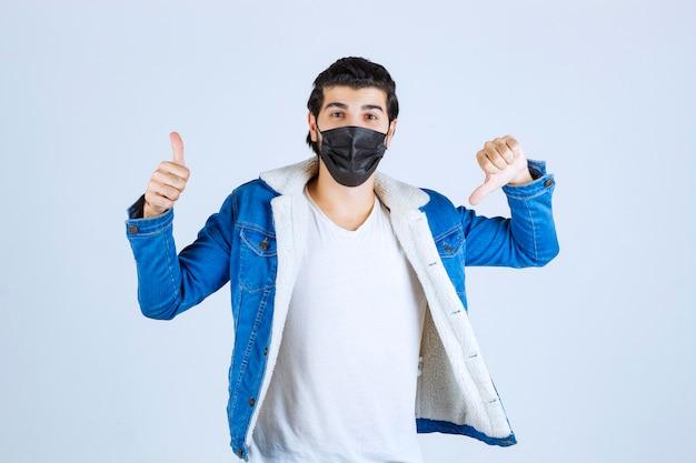 Mężczyzna w czarnej masce pokazujący znak przyjemności i dobre samopoczucie.