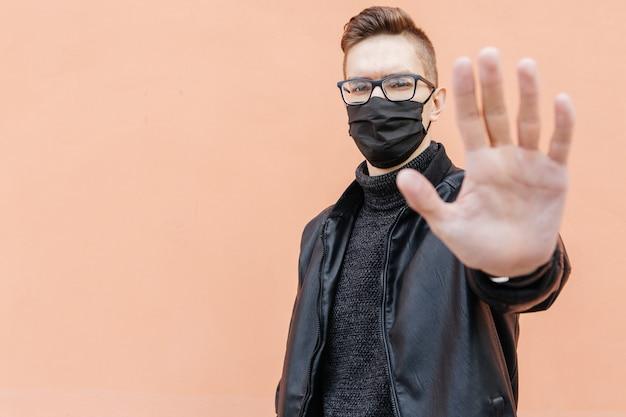 Mężczyzna w czarnej medycznej masce i czarnej kurtce na brown tle pokazuje przerwa sygnał