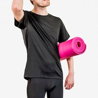 Mężczyzna w czarnej sportowej koszuli z różową matą do jogi