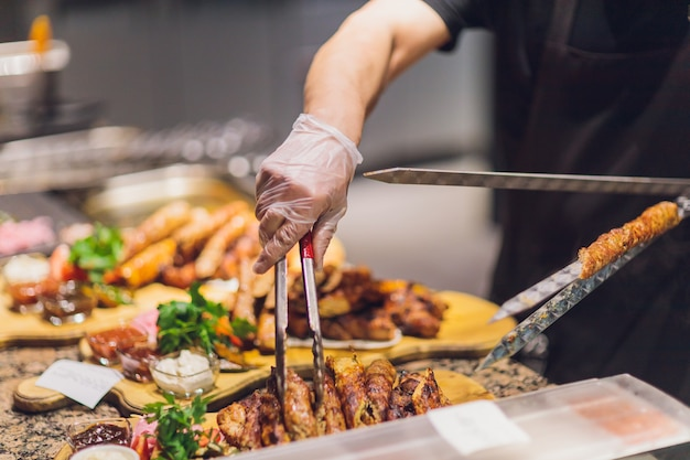 Mężczyzna w czarnych rękawiczkach położył jagnięcinę łopatką do jedzenia na białym talerzu. smaczne gotowane brązowe mięso jagnięce.