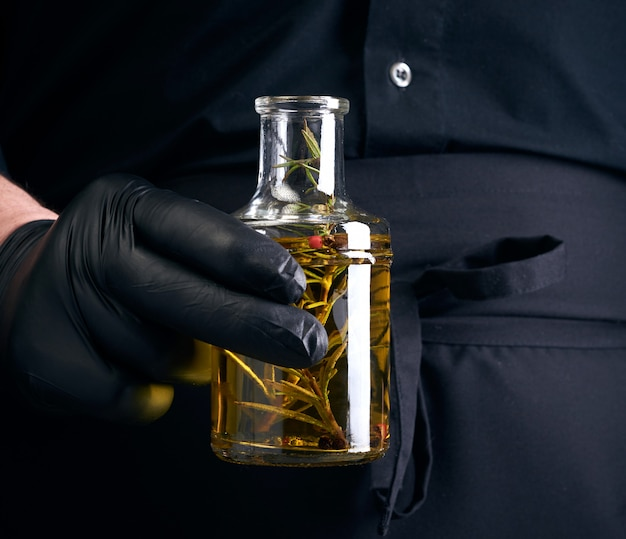 Mężczyzna w czarnych ubraniach, lateksowe rękawiczki trzyma przezroczystą butelkę z oliwą z oliwek