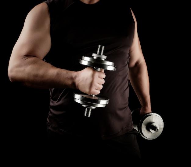 Mężczyzna w czarnych ubraniach trzyma stalowe hantle w dłoniach, jego mięśnie są napięte