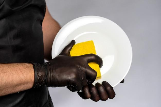 Mężczyzna w czarnym fartuchu i gumowych rękawiczkach trzyma czysty talerz