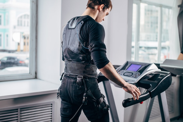 Mężczyzna w czarnym garniturze dla ems szkolenia na bieżni
