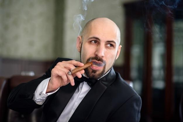 Mężczyzna w czarnym garniturze pali cygaro
