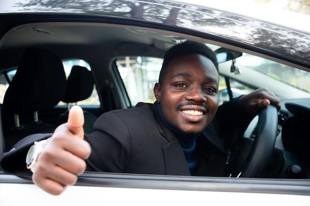 Mężczyzna w czarnym garniturze siedzi za kierownicą, uśmiechnięty i szczęśliwy