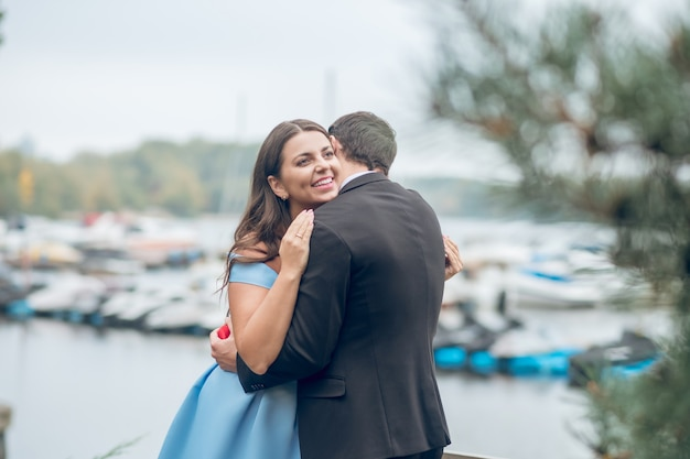 Mężczyzna w czarnym garniturze stojąc tyłem do aparatu przytulanie piękna uśmiechnięta długowłosa kobieta na ulicy