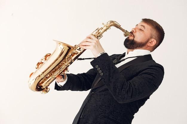 Mężczyzna w czarnym garniturze stojący z saksofonem
