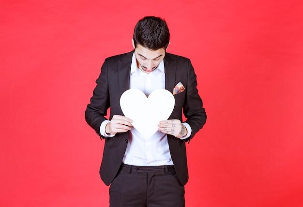 Mężczyzna w czarnym garniturze trzyma białe serce.