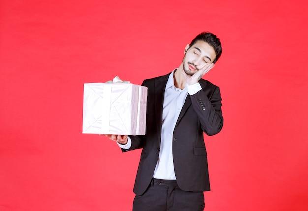 Mężczyzna w czarnym garniturze trzyma fioletowe pudełko i wygląda na zmęczonego i śpiącego.