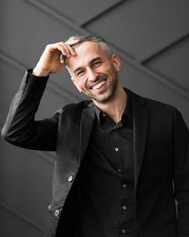Mężczyzna w czarnym garniturze, trzymając rękę na czole