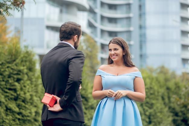 Mężczyzna w czarnym garniturze ukrywa prezent w czerwonym pudełku za plecami i uśmiecha się zainteresowana ładną kobietą w sukience na zewnątrz