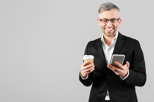 Mężczyzna w czarnym garniturze uśmiecha się do swojego telefonu komórkowego