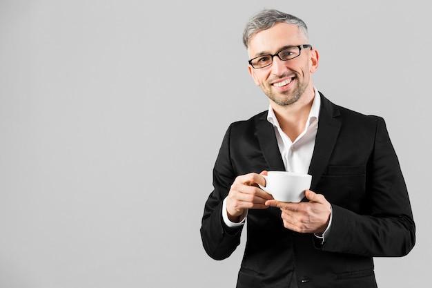 Mężczyzna w czarnym garniturze w okularach i trzyma kawę