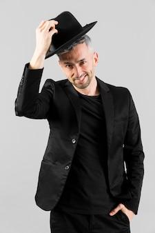 Mężczyzna w czarnym garniturze wita kapelusz