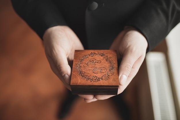 Mężczyzna w czarnym garniturze z rękami trzyma grawerowane brązowe drewniane pudełko