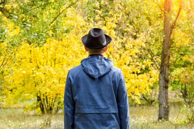 Mężczyzna w czarnym kapeluszu stoi w lesie. koncepcja jesień. widok z tyłu