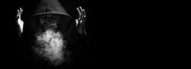 Mężczyzna w czarnym kapturze i dymie na czarnym tle