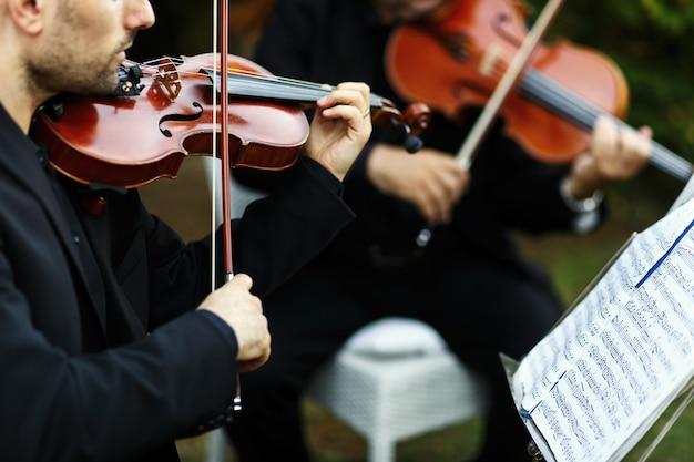 Mężczyzna w czarnym kostiumie gra na skrzypcach