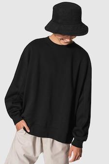 Mężczyzna w czarnym swetrze i czarnym wiaderkowym kapeluszu strzelać do odzieży młodzieżowej