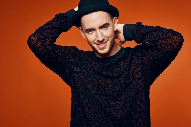 Mężczyzna w czarnym swetrze z kapeluszem w nowoczesnym stylu studio mody