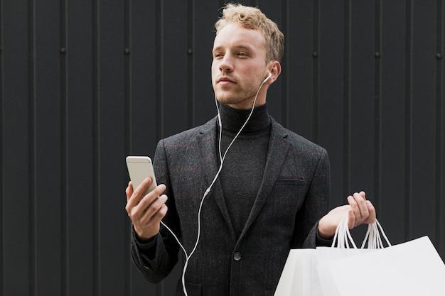 Mężczyzna w czerni z torba na zakupy i smartphone