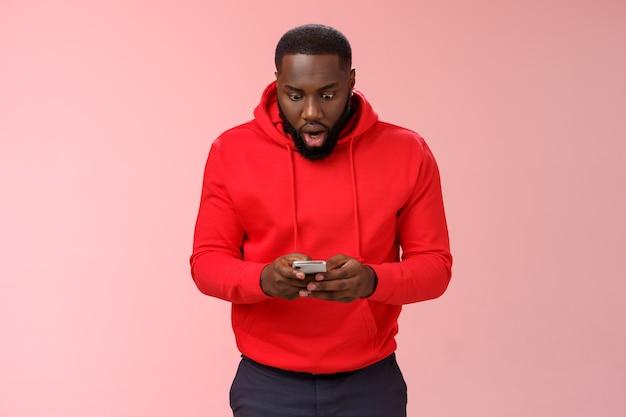 Mężczyzna w czerwonej bluzie nad różem