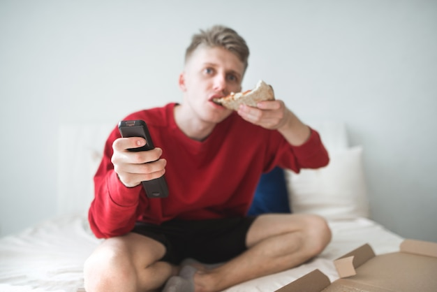 Mężczyzna w czerwonej bluzie siedzi w domu na łóżku