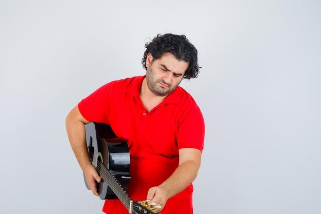 Mężczyzna w czerwonej koszulce gra na gitarze i patrząc skupiony